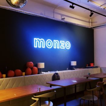 A moody photo of the Monzo office after hours. The Monzo sign is glowing light blue, and there are carved pumpkins underneath it. Spooky Halloween!