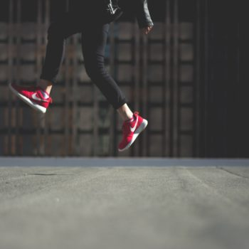 person wearing pair of red Nike shoes, jumping.