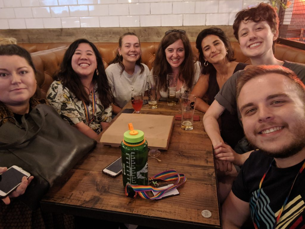 A group of people in a selfie around a table, all smiling at the camera.